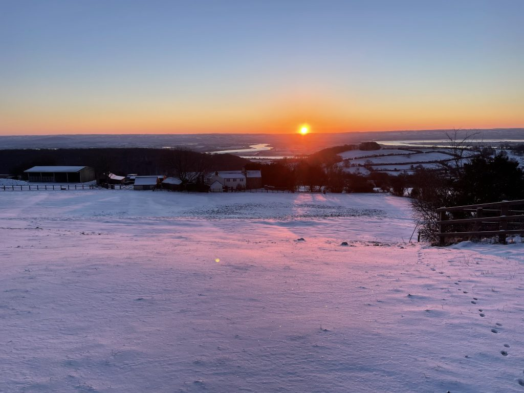 Sun rise over the River Severn with a snow covered field in the foreground.