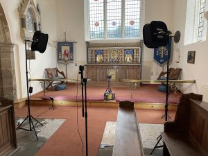 A church chancel with video lights and a camera setup for filming.